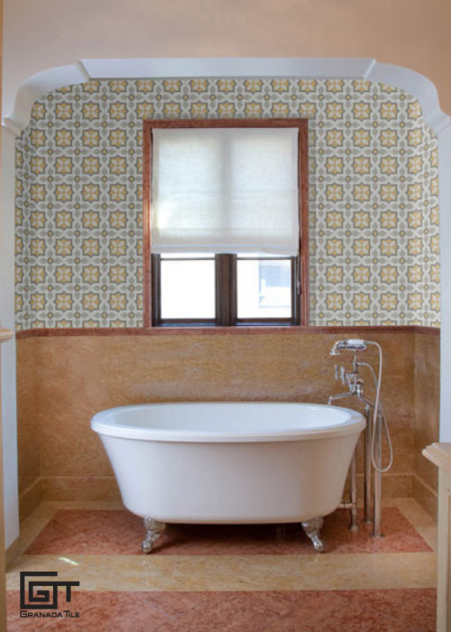 A bathroom with a white bathtub and encaustic cement tiles walls