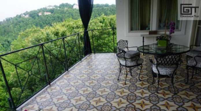 A covered balcony with encaustic tiled flooring, a table, and 3 chairs