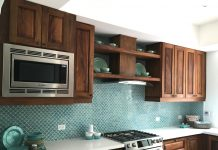 A kitchen with brown cabinets, white countertops, and a wall with scale cement tile