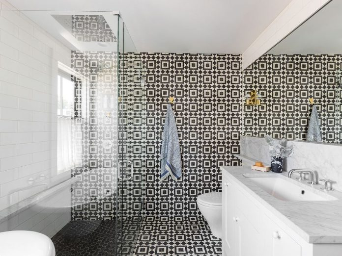 The floor and back wall of a bathroom covered with Granada Tile's Slate-and-white Fez 928 tile