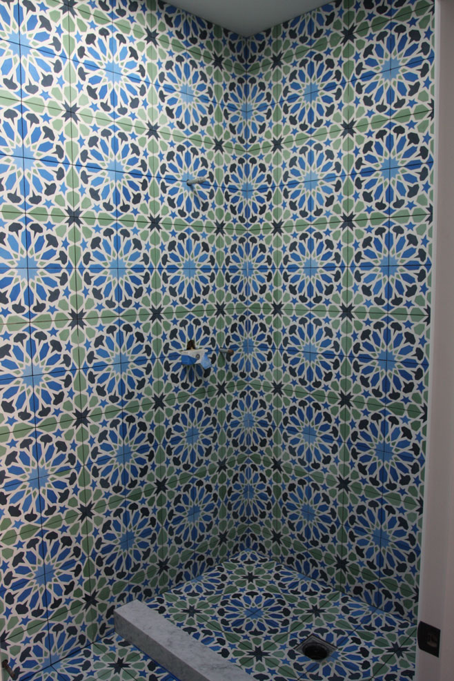 Moroccan motif cement tiles on 2 walls and floor of shower
