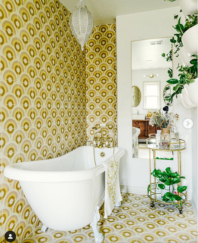Sunny bathroom with floor and wall covered by nested arches in several shades of yellow