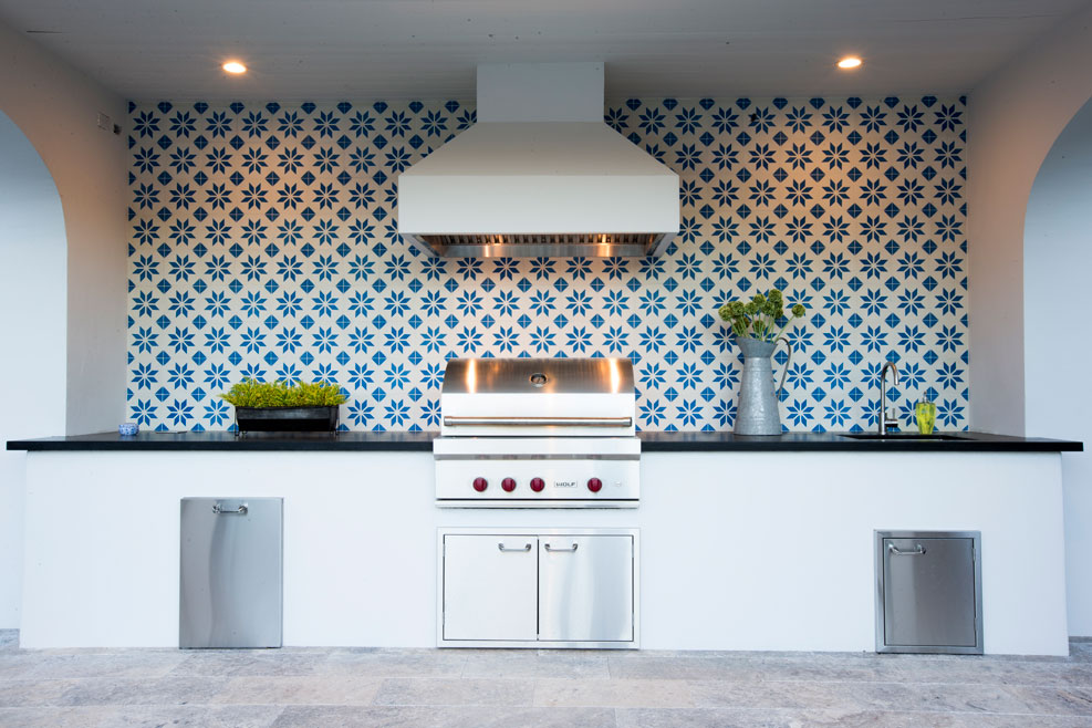 Large backsplash of blue and white geometric tiles in outdoor barbecue area