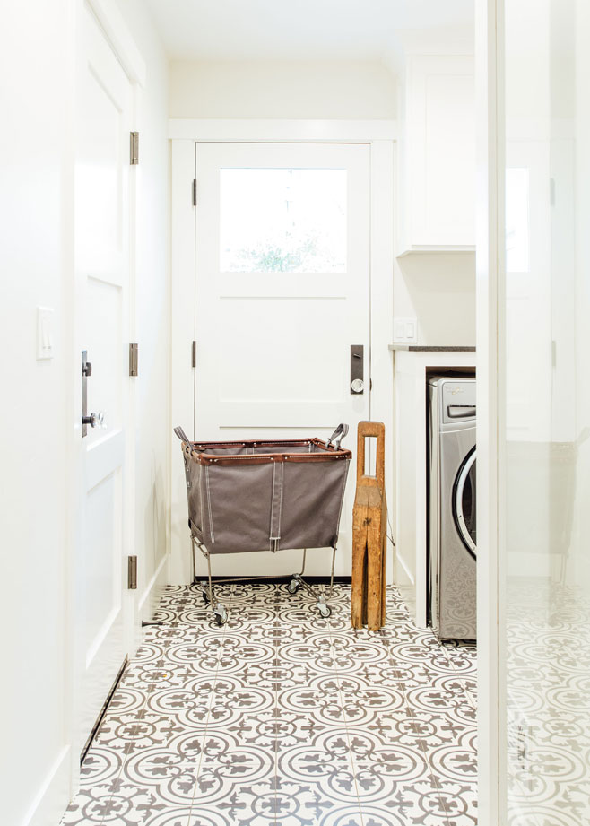 White laundry room with black and white graphic tiles on the floor