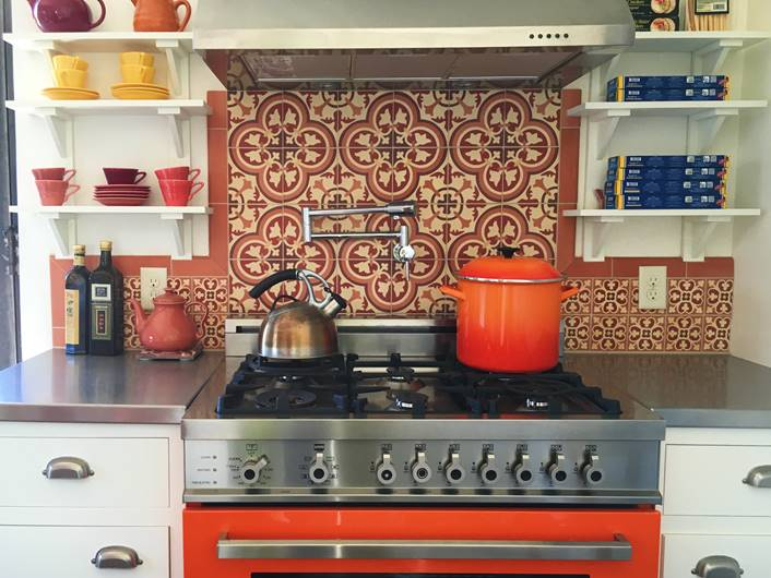 A close up of an oven and the color-coordinated tiles on the backsplash