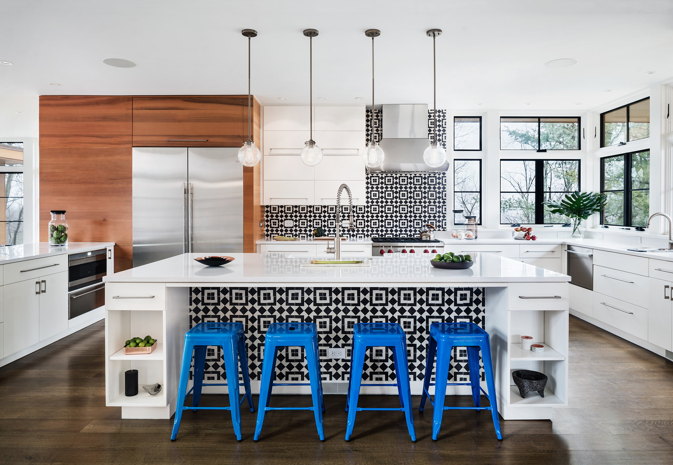 Elegant modern kitchen with black and white geometrical tiles on island bar face and backsplash
