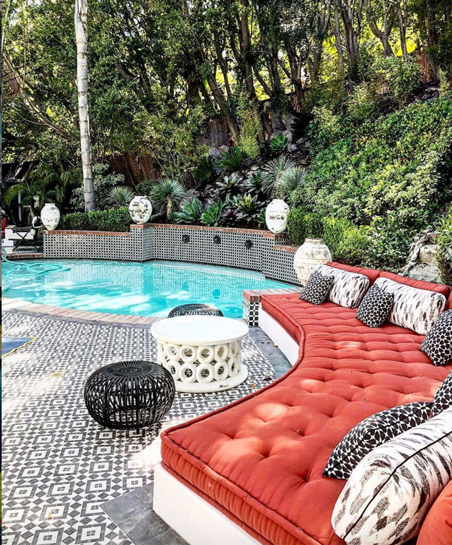 Swooping red couch and pool on a deck of black and white Moroccan-style tiles from Granada Tile