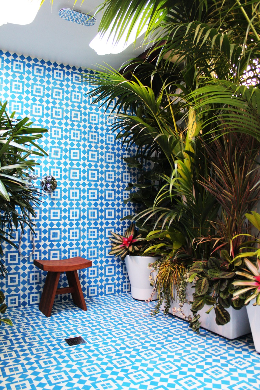 A large bathroom covered in a blue and white geometric tile and filled with luxurious plants