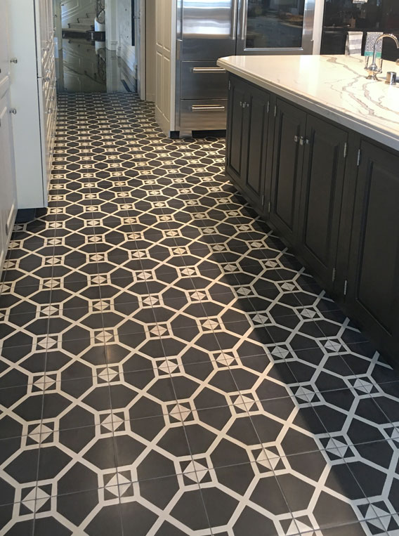 Kitchen with long swath of black and white tile with geometric pattern