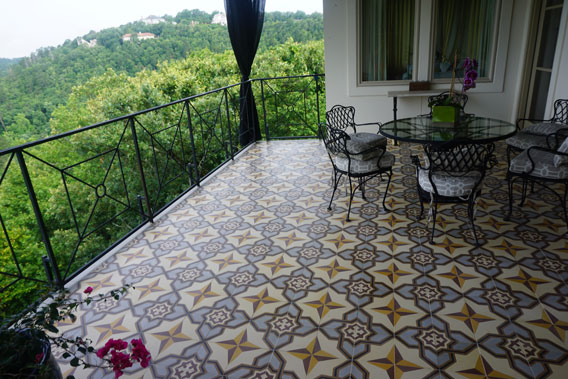 Deck surrounded by woods uses cement tiles to create a harmonious effect