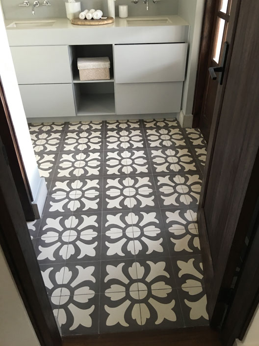 Large flowered floor tiles in black and white define bathroom