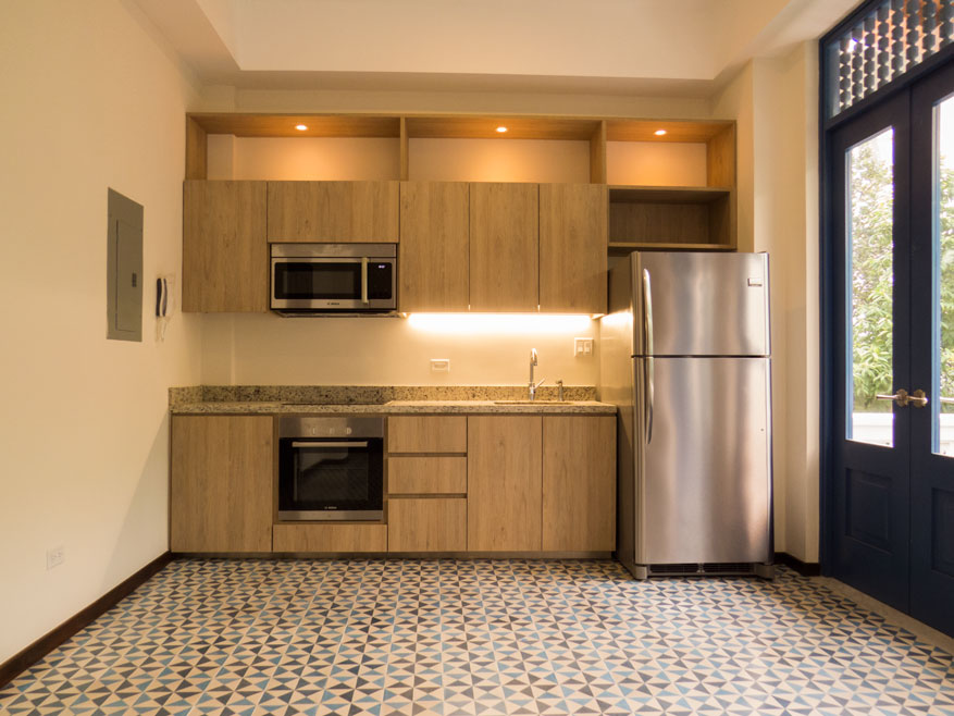 Compact kitchen with a wide stretch of cement tiles on the floor