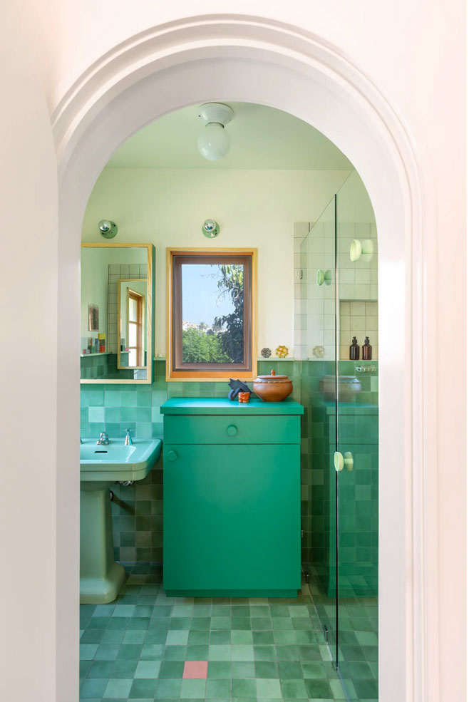 Seen through an archway, this bathroom is a rich study in green tones from the floor to wall cement tiles to the sink and cabinet
