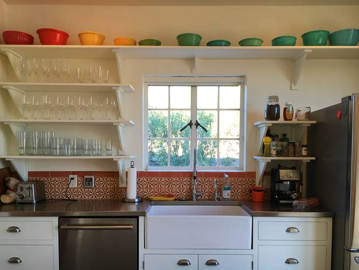 A kitchen that was beautifully curated including a set of color coordinated dishes and custom colored tiles