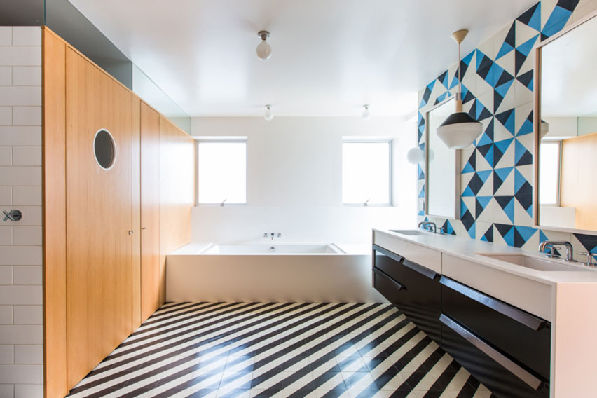 Superb modern bathroom with bold striped floors and playful triangle patterned tile above the sink.