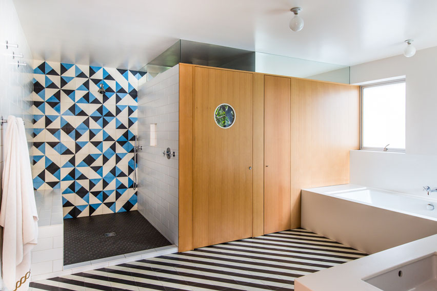 Superb modern bathroom with bold striped floors and playful triangle patterned tile in the shower.