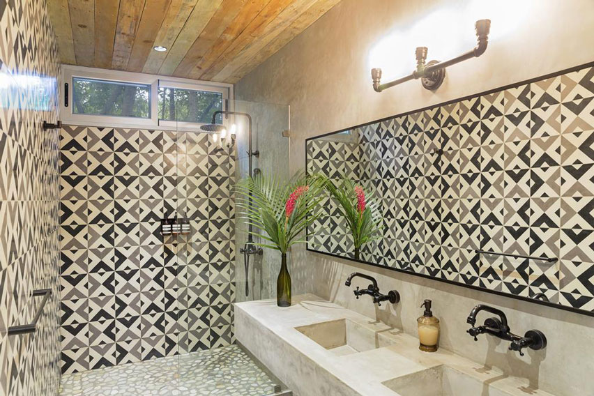 Exciting bathroom in beach retreat created by geometric tile on walls.