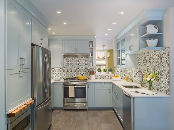 The delicate blue of pale blue cabinets in a modern traditional kitchen is echoed in the Cluny cement tile backsplash