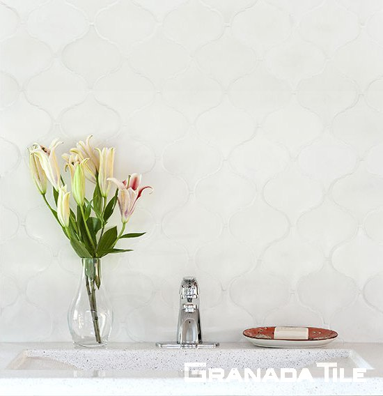 Granada Tile company's Andalucia Arabesque cement tile adds a subtle undulating shape in classic clean white bathroom